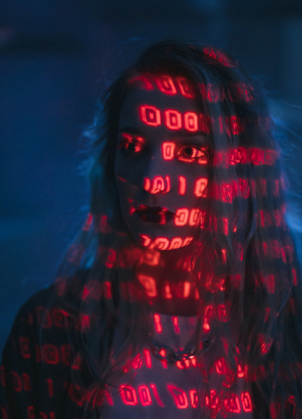 Woman in front of blue background - she has red binary code projected onto her face